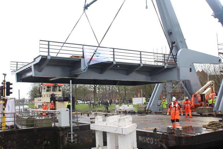 Het brugdek wordt voorzichtig op de pijlers gelegd.