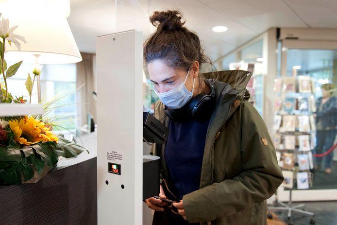 Verslaggever Fleur Reijngoudt test de SmartXcan Multisensor in de hal van 't Dijkhuis in Bathmen.