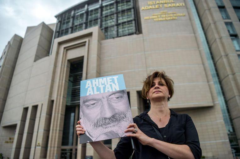 Een journalist met het portret van de Turkse journalist Ahmet Altan in 2017. Beeld null