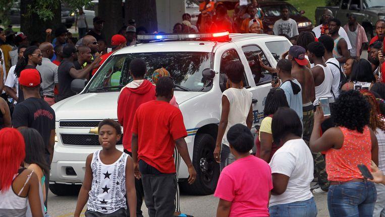 Demonstranten houden een politieauto tegen in Ferguson. Beeld ap