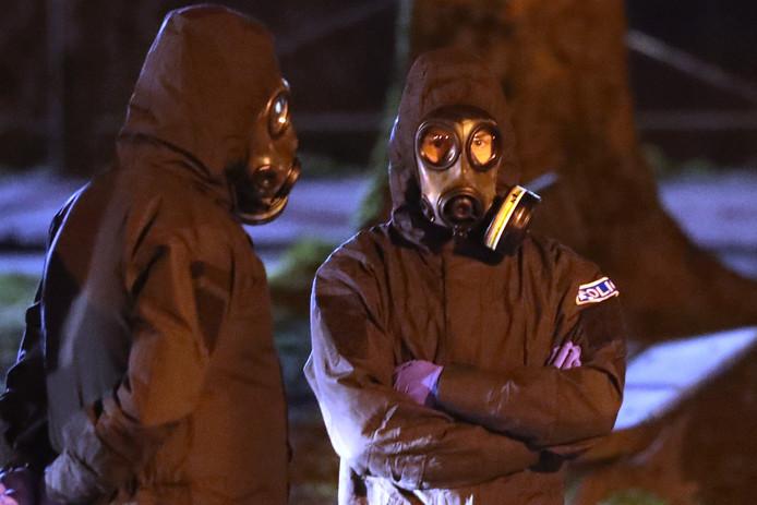 Politieagenten in beschermende pakken werken op de plek van de zenuwgasaanval.