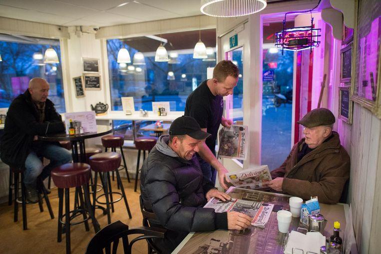 De Haagse marktkoopmannen Ro (l) en Bert Dispa krijgen de krant van Luck Rietveldt Beeld Mats van Soolingen