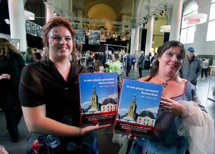 Gastvrouwen Josine ( links) en Vera van de expositie Kunsten Onder 1 Dak in de St. Jan tonen het boek  'In een plaats genaamd Roosendaal'.