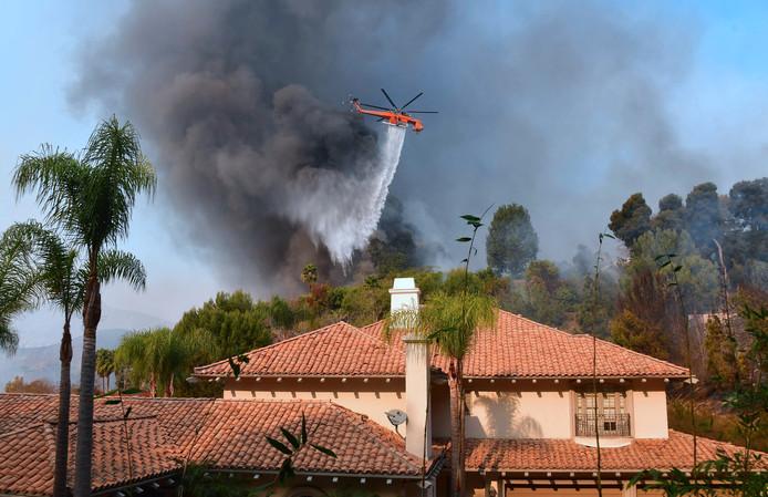 Een blushelikopter vliegt boven de villawijk Bel Air om de bosbranden te bestrijden.
