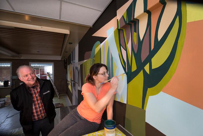 Jan Willem Hoopman kijkt toe hoe kunstenares Judith Woordes de laatste hand legt aan de metersgrote wandschildering in de kantine van zijn bedrijf in IJzerlo. Foto: Theo Kock