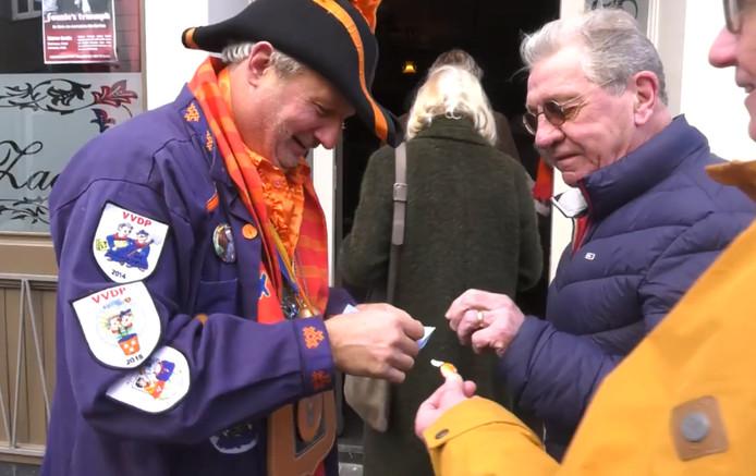 Oud-prins van ut Kielegat Peterus C Lie d'un Alleraller Irste deelt nummertjes uit voor de voorverkoop van de carnavaleske wandeling.