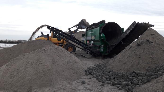 Het zand wordt met een graafmachine in een draaiende trommel gekiept om klei en andere ongerechtigheden eruit te 'zeven'.