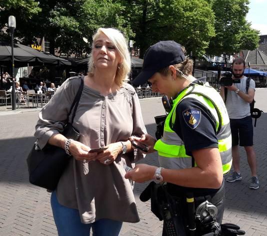 Pegida-lid Asje Bello wordt gecontroleerd door agenten op de Oude Markt