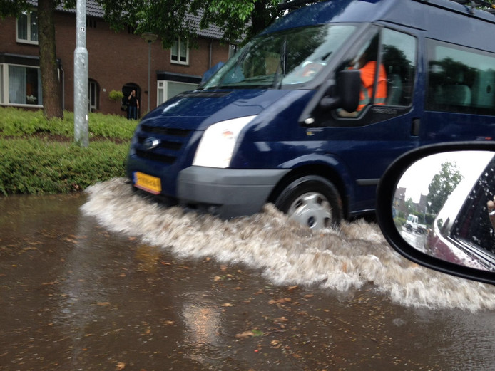 Een busje rijdt over de ondergelopen Julie Postelsingel in het centrum van Boxmeer.