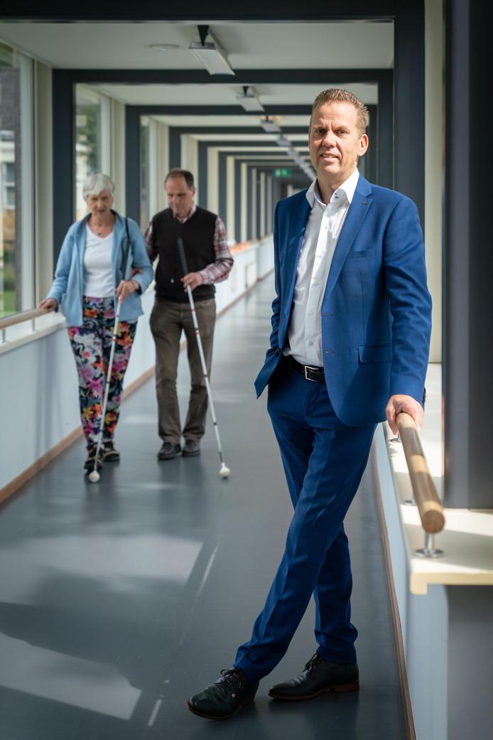 Directeur Frank van der Eijnden van Het Schild, woonzorgcentrum voor blinden en slechtzienden in Wolfheze. Op de achtergrond loopt het echtpaar Polderman. Deze huurders van aanleunwoningen zijn tevreden over het woon-zorgklimaat in Het Schild.