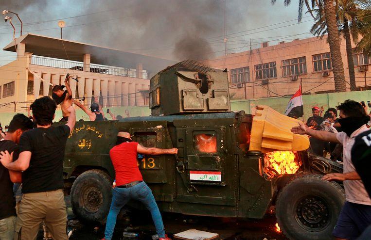 Betogers steken een politievoertuig in brand tijdens protesten tegen de overheid in Bagdad. Beeld AP