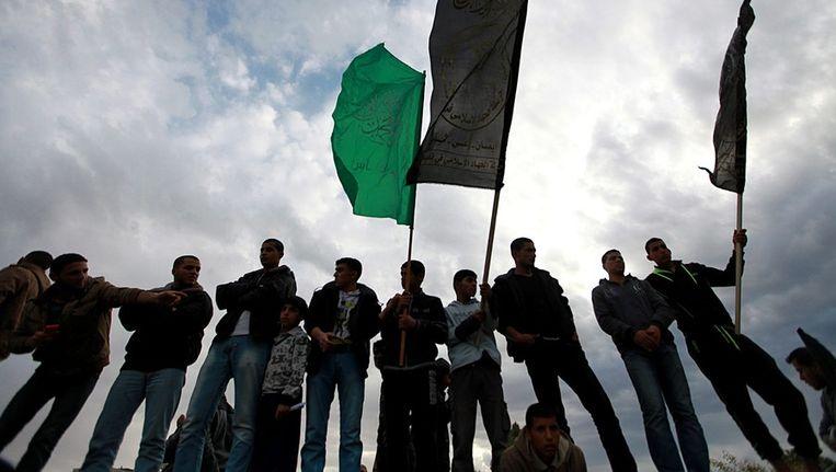 Palestijnse jongeren houden vlaggen omhoog van Islamic Jihad (R) and Hamas (L) tijdens een begrafenis van Jihad-strijders. Beeld afp