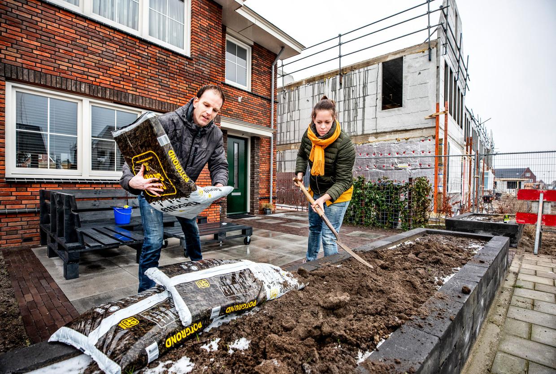 John Zwinkels en Miriam Zwinkels-Broch aan het werk in de voortuin van hun nieuwe huis in de wijk Woerdblok in Naaldwijk.  Beeld null