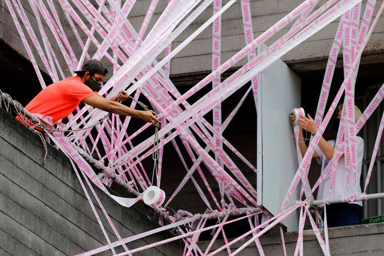 Een vrijwilliger van #MissingLiveTheater hangt tape over het National Theatre in Londen. Beeld AFP