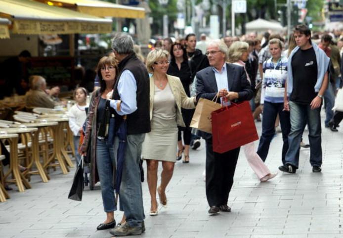 Foto ter illustratie van winkelend publiek in de winkelstraat Koenigsallee in Düsseldorf
