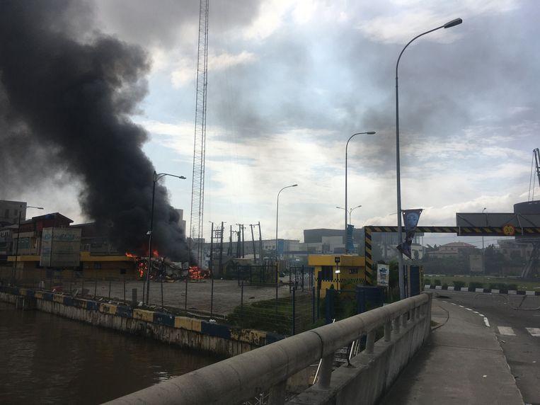 Een gebouw aan de Lekki tolpoort in Lagos staat in brand. Dit gebeurde nadat soldaten in de menigte van demonstranten hadden geschoten, met doden en gewonden tot gevolg.   Beeld AFP