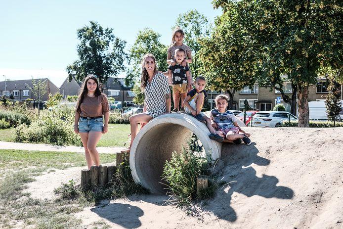 Nicole Schouten van Driestroomhuis Het Kom-Fort met een aantal kinderen bij de rioolbuis in de speltuin aan de Lupinestraat.
