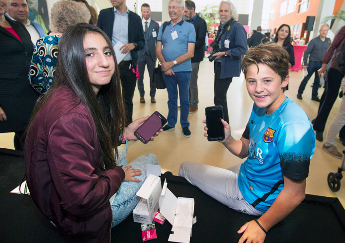 Staatssecretaris Klijnsma (r) geeft Ayasolange Hamarasheed (l) en Anastacia Dekker hun mobieltje.