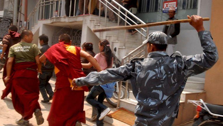 Tibetaanse monniken worden opgejaagd door de Nepalese politie in 2008. Beeld ANP