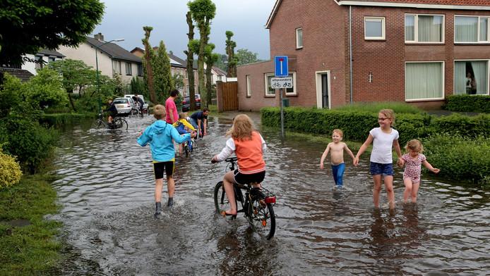 Kinderen in een ondergelopen straat na de flinke regenval van afgelopen week.