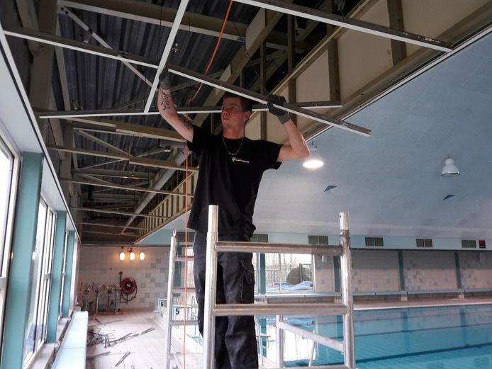 Het verwijderen van de oude plafondplaten in zwembad De Kiefer.
