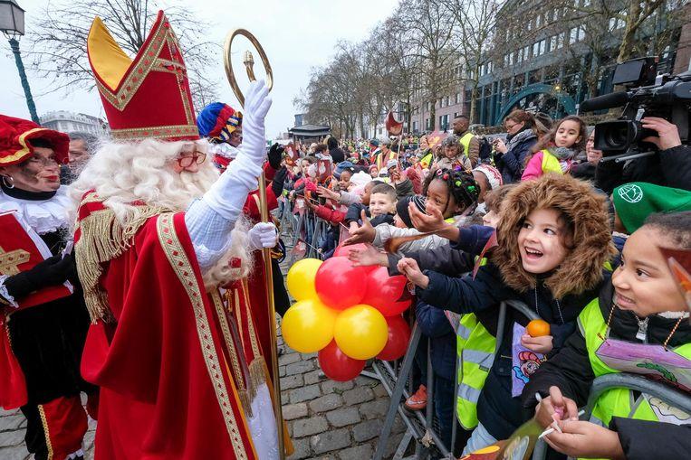 Sinterklaas groet de kindjes die hem toejuichen.