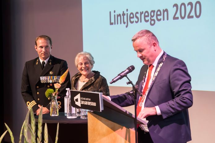 Mien Glaser-van der Spek krijgt een lintje, haar zoon Stephan heeft er al veel op zijn borst. Rechts burgemeester Mark van Stapperhoef van Goirle.