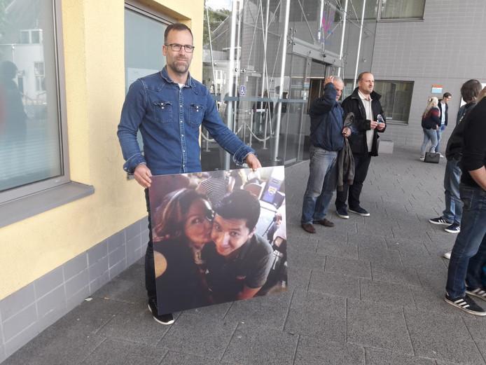 Bas Wolferts, zwager van de omgekomen vrouw, staat voor de rechtbank in Middelburg met een portret van beide slachtoffers .