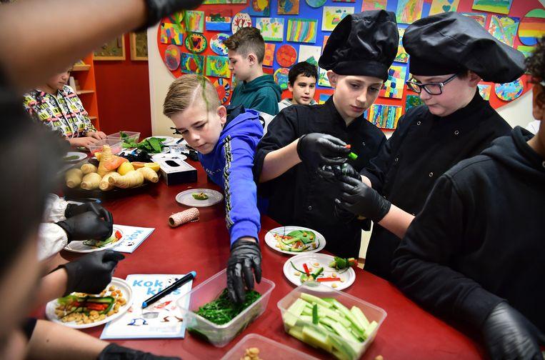 Leerlingen van groep 8 van basisschool Mozaiek krijgen een les over koken en eten.  Beeld Marcel van den Bergh