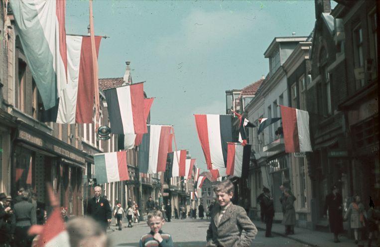Purmerend, 5 mei 1945. In de Peperstraat in het oude centrum wordt na de aftocht van de Duitse militairen gevlagd. Een dag later arriveren de Canadese troepen in de stad. Beeld Dirk Bakker/Collectie Vereniging Historisch Purmerend