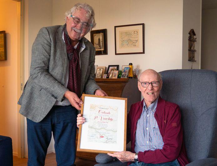 Piet Voorsluijs (92) toont de oorkonde die hij krijgt uitgereikt door Steef Staal.