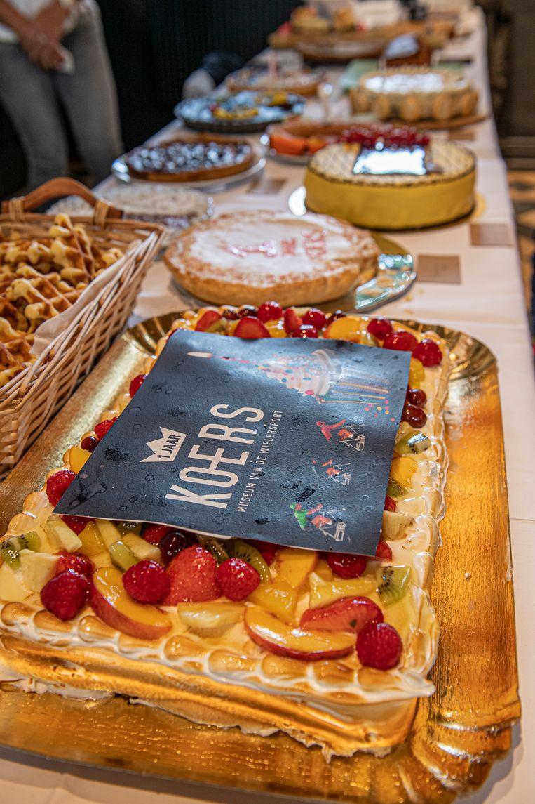 Een lange tafel vol met heerlijke taarten.