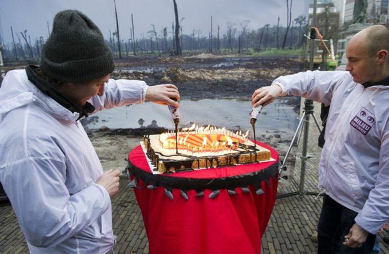 Actievoerders van Milieudefensie gieten 'olie' in de vorm van chocoladesaus over een taart met het logo van Shell, 2010. Beeld ANP