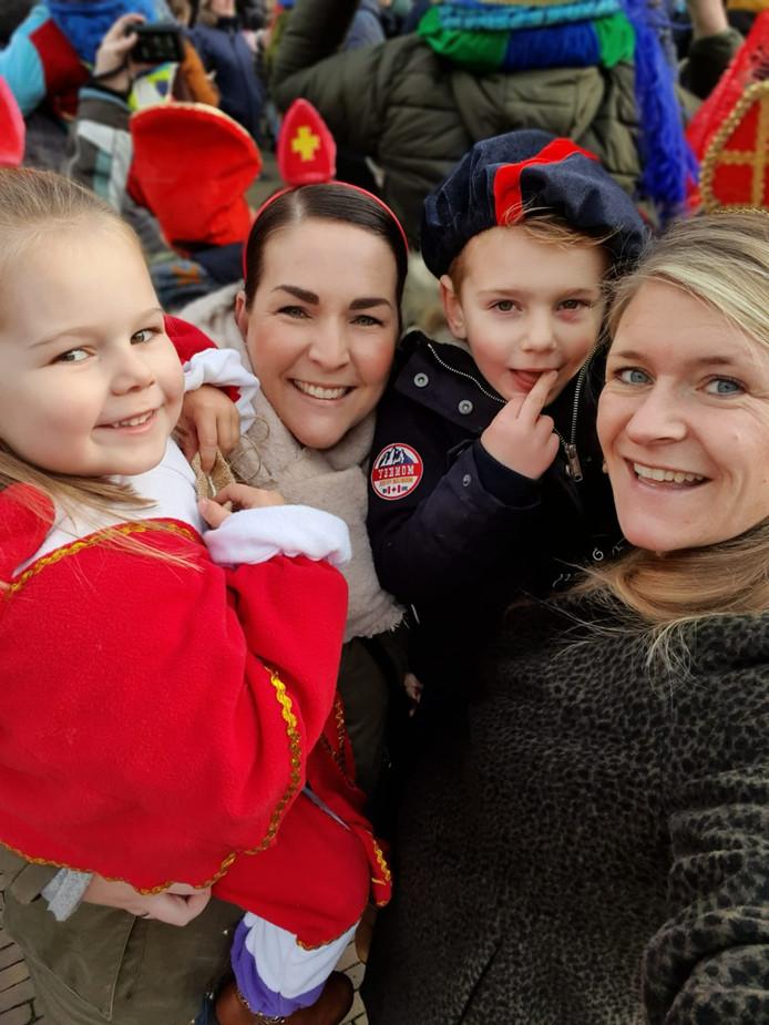 Fenne (links) en Siem genieten met hun mama's bij de intocht in Gorinchem.