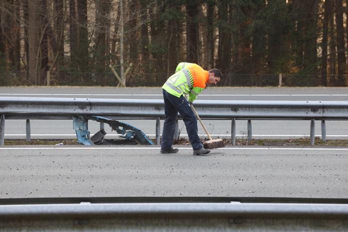 Een medewerker van Rijkswaterstaat veegt de snelweg schoon.