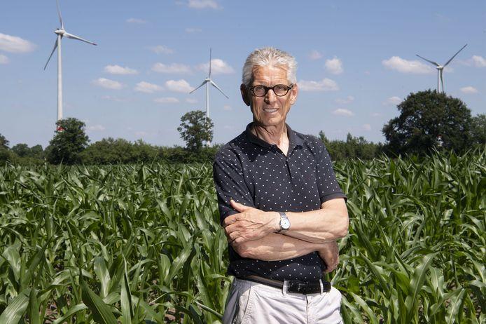 Hans te Grotenhuis, voorzitter Burgerwindcoöperatie Achterhoekse Wind Energie, met op de achtergrond windmolens bij Ammeloe net over de Duitse grens.