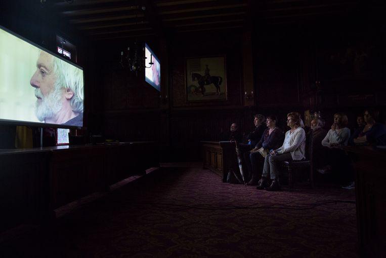 Onder meer Jenny Nijsten (eerste stoel vooraan), de weduwe van Miel Cools, kijkt geëmotioneerd naar de film.