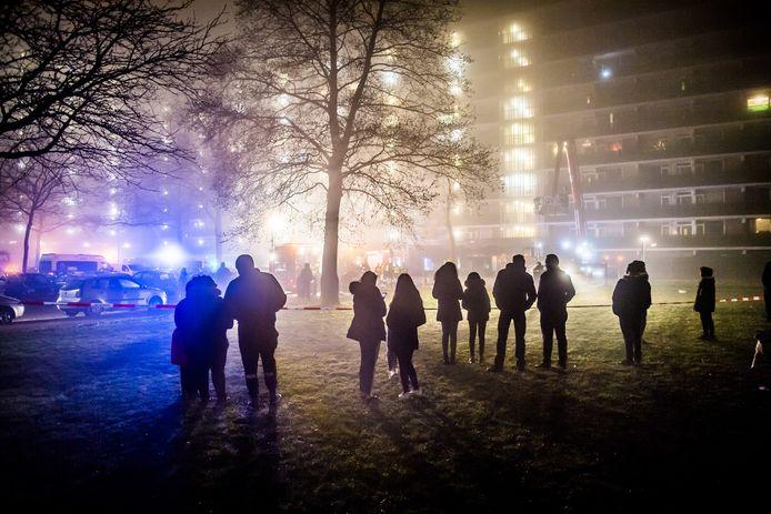 Mensen kijken naar de brand in de flat aan het Gelderseplein in Arnhem.