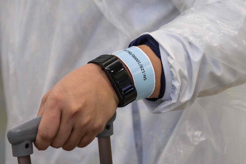Reizigers die in Hongkong arriveren, krijgen een quarantaine-armband met een locatietracker. Beeld AFP