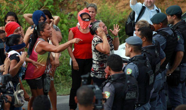 Familie van gevangenen staan tegenover de politie voor de gevangenis in de stad Manaus. Beeld reuters