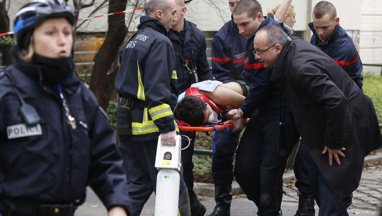 Hulpverleners brengen een slachtoffer weg na de aanslag op het weekblad Charlie Hebdo in Parijs.