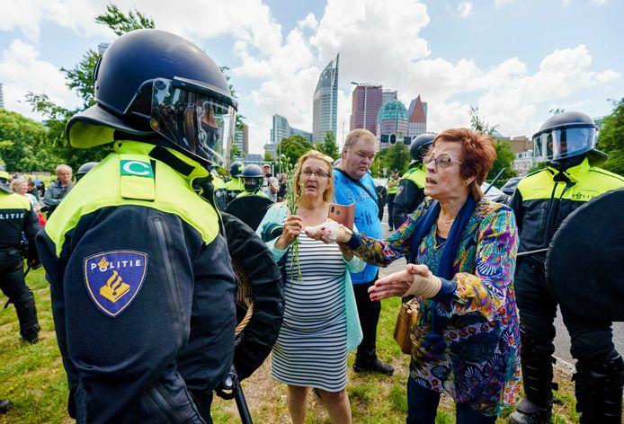 Demonstranten in discussie met de ME bij de verboden demonstratie van Viruswaanzin op het Malieveld die is gericht op de coronamaatregelen van het kabinet.