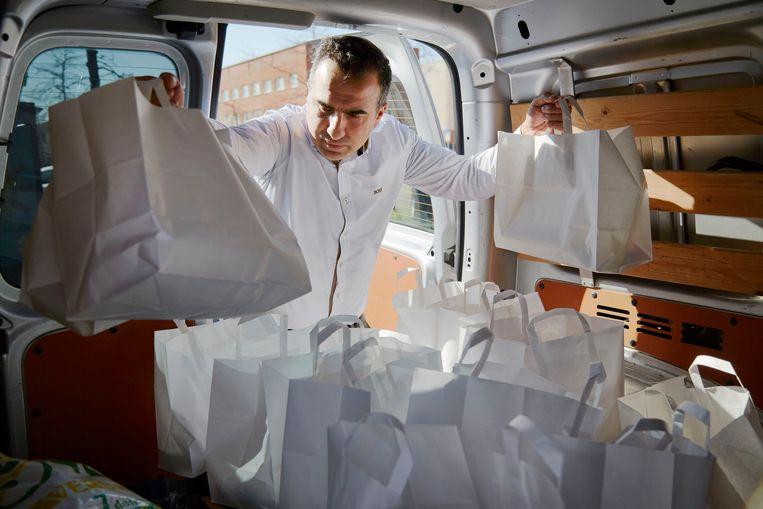 Atalay Celenk deelt maaltijden uit. Beeld Getty Images