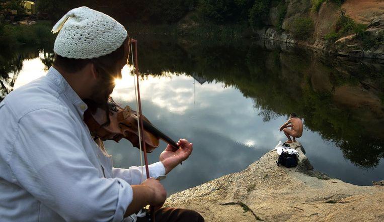 Een man speelt viool terwijl de andere man op de foto een rituele wassing ondergaat. Beeld EPA