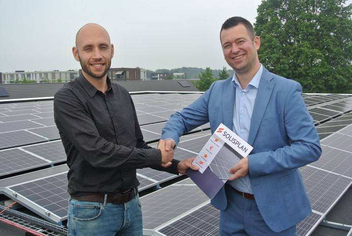 Directeur Teun van Sinten van Solisplan Group BV en wethouder Toine van de Ven bovenop het dak van de sporthal van IKC De Avonturier.