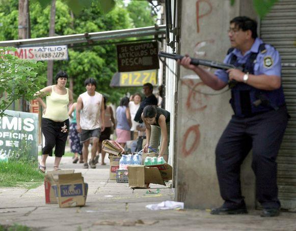 Archiefbeeld. Een politie-agent probeert een buurtsuper te beschermen tegen plunderaars. (19/12/2001)