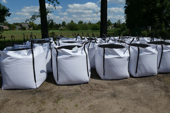 Zakken vol rubber korreltjes staan klaar voor vervoer naar Doetichem.