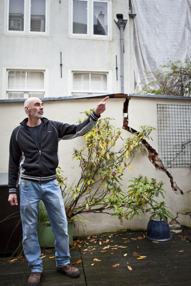 Arend Meischke bij de scheuren in zijn terrasmuur. Foto Marc Driessen Beeld