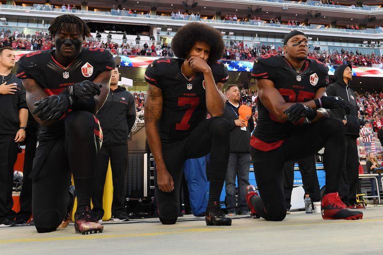 Terwijl het volkslied klinkt voorafgaand aan hun wedstrijd knielen Colin Kaepernick (midden) en zijn teamgenoten Eli Harold (links) en Eric Reid uit protest tegen racisme, oktober 2016. Beeld AFP