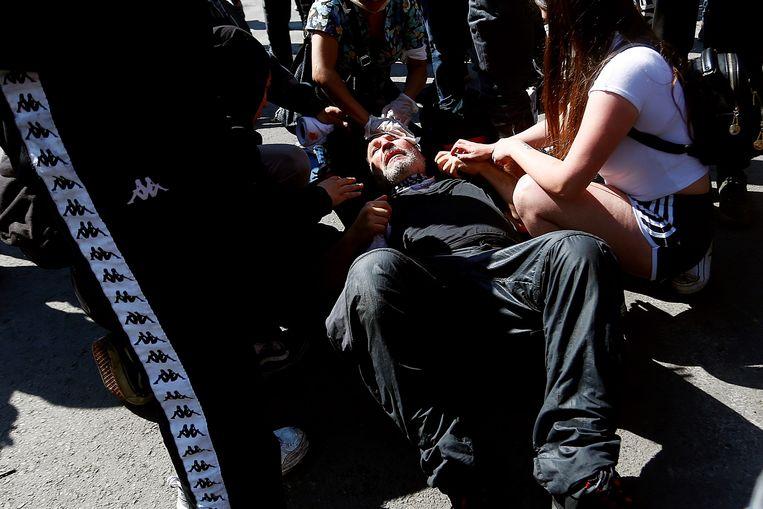 Een gewonde man krijgt medische hulp toegediend nadat hij geslagen is door politieagenten in Santiago de Chile.